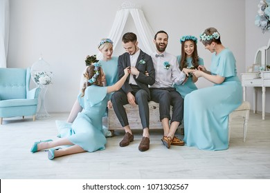 Gay wedding. Two handsome grooms sitting on the bed in the luxury hotel room with their female guests clad in similar blue dresses.  One newlywed laughing while showing his wedding ring to girls.