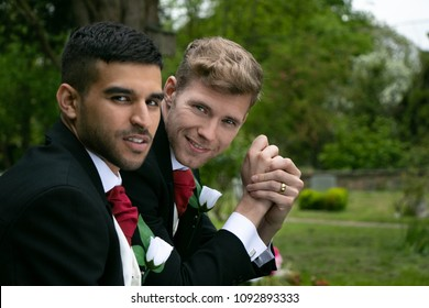 Gay weddings, grooms, couples pose for pictures after their wedding ceremony in churchyard