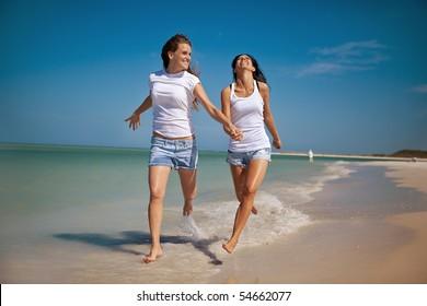 Gay women running at the beach