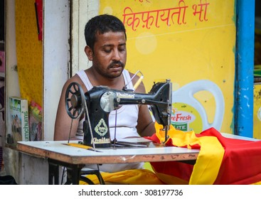 Gaya, India - Jul 22, 2015. Portrait of Indian man tailor at work place with sewing machine at the market in Bodhgaya, India.