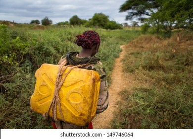 GAYO VILLAGE, ETHIOPIA - JUNE 19: Woman with a can of water from a nearby well (called Ella) on her way back to her village on June 19, 2012 in Gayo village, Ethiopia.