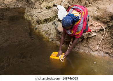 GAYO VILLAGE, ETHIOPIA - JUNE 19: Woman takes water from a well before returning to her village. The water is purified with tablets before drinking on June 19, 2012 in Gayo village, Ethiopia.