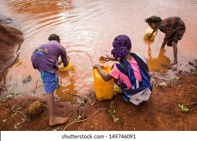 GAYO VILLAGE, ETHIOPIA - JUNE 19: Women and young village girls collect water from a rain water pool which is purified before use with tablets. on June 19, 2012 in Gayo village, Ethiopia.