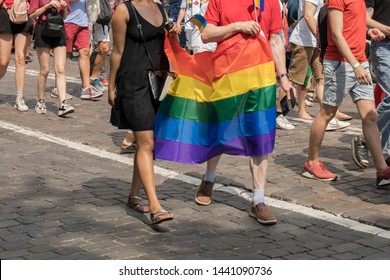 GayPride spectators with rainbow color flag during Pride parade. Rainbow colors cloth