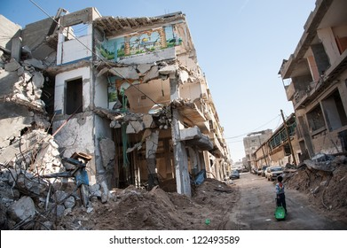 GAZA, PALESTINIAN TERRITORY - DECEMBER 2: A child passes a bombed-out residential block in the Al-Zeitoun neighborhood of Gaza City, December 2, 2012.