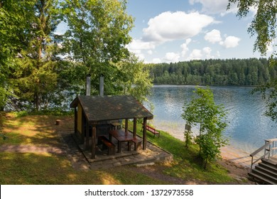 Gazebo for barbecues in the woods by the lake in the summer