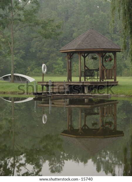 A gazebo and canoe reflected in a pond.