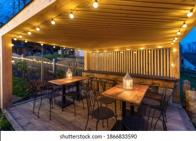 Gazebo with lights at night. Picture of a summer house with comfortable garden furniture. Romantic scene in dusk. - Shutterstock ID 1866833590