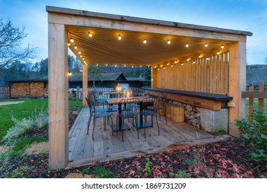 gazebo with lights at night. Picture of a summer house with comfortable garden furniture. Romantic scene in dusk.