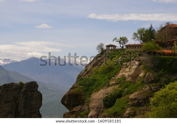 A gazebo  on top of a steep cliff at meteora Greece and snowed mountains in the background