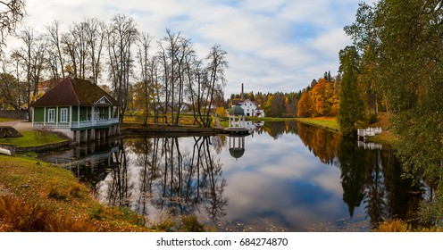 Gazebo (rotunda) on the shore of pond with other resindential buildings. Estonian manor. Autumn time.