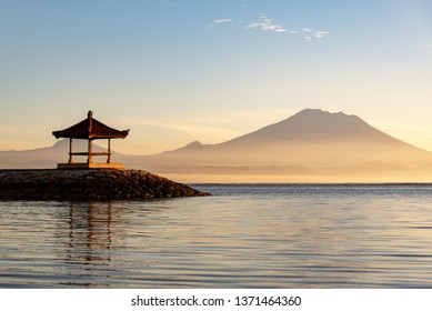 Gazebo at Sanur beach with Mt Agung volcano background during sunrise located in Bali Indonesia