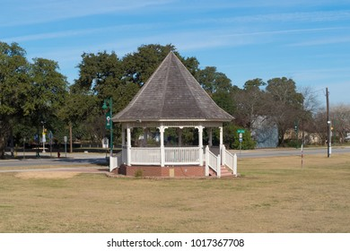 a gazebo surrounded by almost colorless winter grass