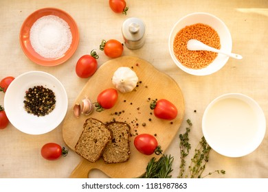 Gazpacho soup in rustic metal bowl with fresh tomatoes, green sauce, chili, garlic and basil over rustic white wooden backdrop. Top view, copy space, horizontal