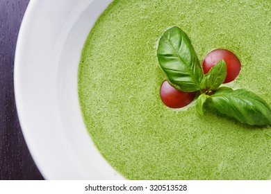Gazpacho spinach with basil leaves and tomatoes on desk