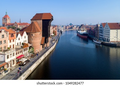 Gdansk old city in Poland with the oldest medieval port crane (Zuraw) in Europe,  St John church, Motlawa River, old  granaries, ship and yacht. Aerial view in early morning. Sunrise light.