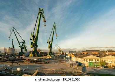 Gdansk, Poland - 05.06.2017: Ship loading cranes old port of Gdansk by Baltic sea. Beautiful Industrial scene in golden light.