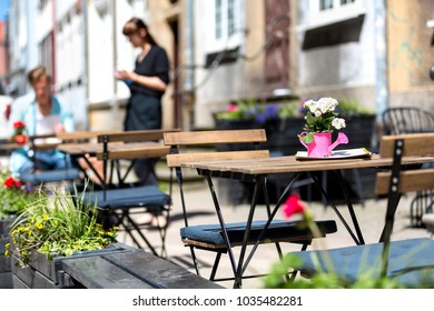 Gdansk, Poland, 2017 05 22: tables and chairs on the street - waitress and client in the background