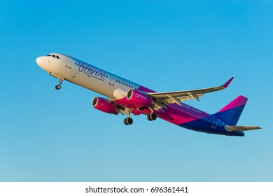 GDANSK, POLAND - AUGUST 13, 2017: Passenger airplane of Wizz Air airlines in the air, flying on the clean blue sky. Wizzair is a Hungarian low cost airline.