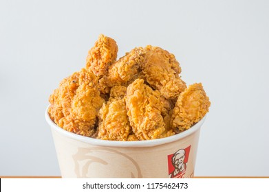 Gdansk, Poland - August 24, 2018: A lots of fried chicken hot wings in bucket of KFC (Kentucky Fried Chicken) fast food.