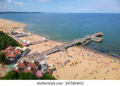 Gdansk, Poland - August 3, 2019: People relaxing on the beach with wooden pier at Baltic Sea in Gdansk, Poland.