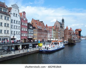 GDANSK, POLAND, EUROPE on JUNE 2017: Historic buildings in medieval port crane (Zuraw) in polish travel Gdansk city landscape, sailing ship at Motlawa River, clear blue sky in warm sunny summer day.