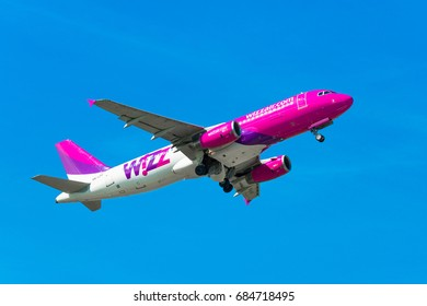 GDANSK, POLAND - JULY 22, 2017: Passenger airplane of Wizz Air airlines in the air, flying on the clean blue sky. Wizzair is a Hungarian low cost airline.