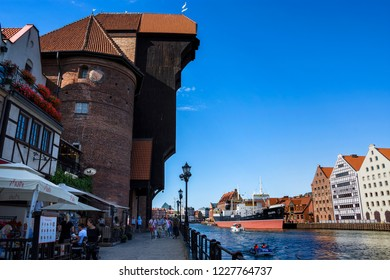 GDANSK, POLAND - JULY 7, 2018. Shore of old harbor,over Motlawa river with historic shore Quayside (Dlugie Pobrzeze) ,the medieval wooden port crane and The Crane (Zuraw), symbol of Gdansk.