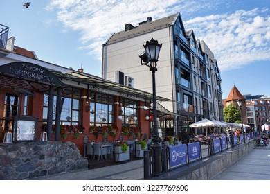 GDANSK, POLAND - JULY 7, 2018. Shore of old harbor, over Motlawa river with historic shore Quayside (Dlugie Pobrzeze) ,the medieval wooden port crane of Gdansk. Dominikanska Restaurant.