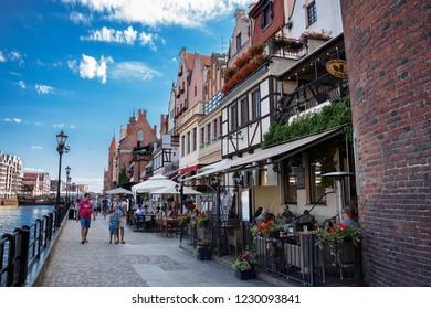 GDANSK, POLAND - JULY 7, 2018. Shore of old harbor, over Motlawa river with historic shore Quayside (Dlugie Pobrzeze) ,the medieval wooden port crane of Gdansk.