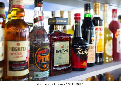 Gdansk, Poland - May 24, 2018: Selection of liqueur bottles on the bar shelf. Selective focus on the Disaronno liqueur bottle.