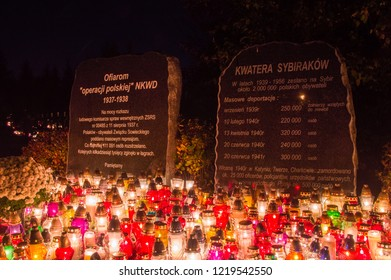 Gdansk, Poland - November 1, 2018: Candles at memorial plaque dedicated to the victims of Polish Operation of the NKVD and memorial plaque dedicated to the Sybiraks at Gdansk Lostowice cemetery.