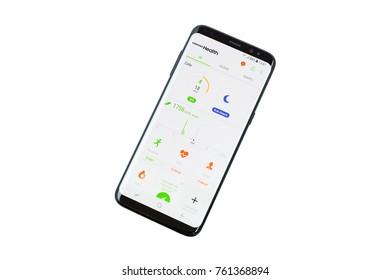 GDANSK, POLAND - NOVEMBER 23, 2017: Brand new black Samsung Galaxy S8 over white background. Samsung Galaxy Health application on the screen.