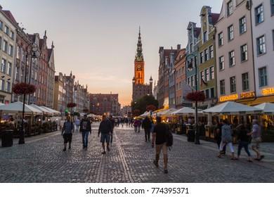 GDANSK, POLAND -  SEPTEMBER 1, 2016: Evening view of people walk along historic houses at Dlugi Targ square in Gdansk, Poland.