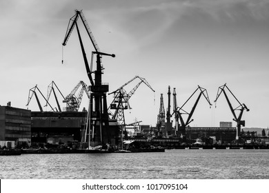 Gdansk shipyard, Poland. Retro style black and white. Cranes, old shipyard buildings, rusty structures.