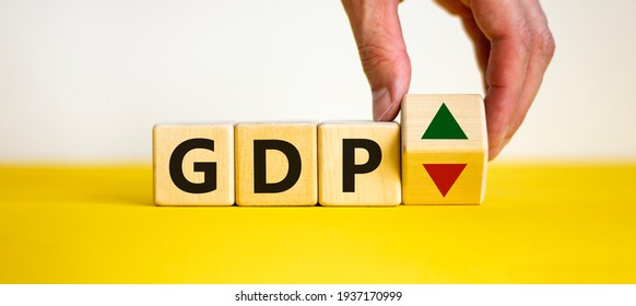 GDP, gross domestic product symbol. Businessman holds a cube with up and down icon. Word 'GDP'. Beautiful white background. Copy space. Business and growth of GDP, gross domestic product concept.