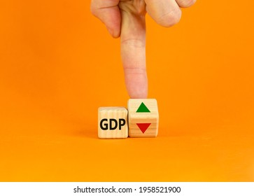 GDP, gross domestic product symbol. Businessman turns a cube with up and down icon. Word 'GDP'. Beautiful orange background. Copy space. Business, growth of GDP, gross domestic product concept.