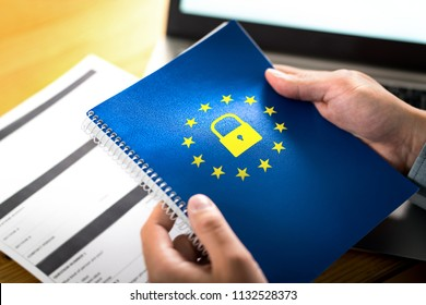 GDPR (General Data Protection Regulation) concept. Business man holding notebook with European Union (EU) flag logo and lock icon. Laptop computer and paper form on desk and table.