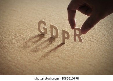 GDPR wood word on compressed or corkboard with human's finger at R letter.