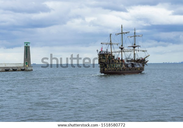 Gdynia, Poland - 7.7.2019: Lighthouse and battle boat horizontal photo on open sea near Gdansk. Vessel with tourists heading from port to cloudy sky on horizon.