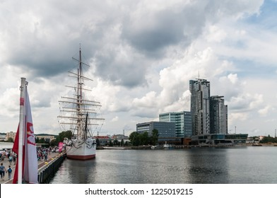 Gdynia, Poland,  August 25, 2018; Frigate docked in port of Gdynia and high rise building in backgroun and polish flag in front in cloud day