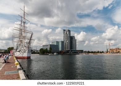 Gdynia, Poland,  August 25, 2018; Frigate docked in port of Gdynia and high rise building in backgroun