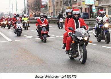 GDYNIA, POLAND - DECEMBER 15: Santas participate in the International Santa Claus motorcycle parade on Dec.15, 2013 in Gdynia, Poland. They stop in the City center and give charity gifts for children
