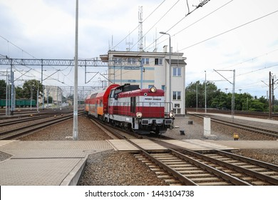 GDYNIA, POLAND - JULY 4, 2019: Diesel locomotive with train cars at the main station in Gdynia, Poland