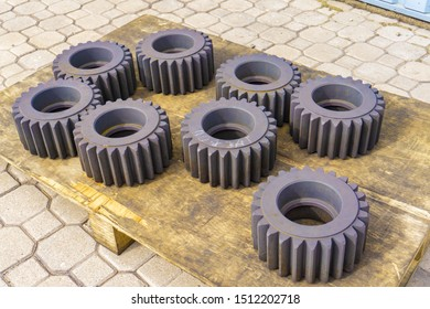 Gear after heat treatment and hardening on a wooden rack, improving the hardness of the metal.