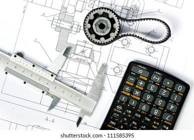 gear, caliper and calculator on blueprint