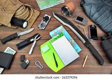 Gear laid Out For Backpacking Trip On  Table. Items Include Rope Bag Backpack  Raincoat Vest Notepad Compass Wallet Money Binoculars Knife Machete Searchlight Flashlight Rope Pen Pencil Mug Map