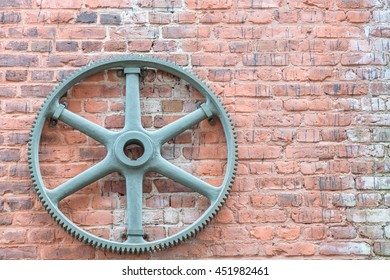 Gear mounted on a brick wall in an industrial area. Pattern