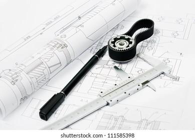 gear, pen and caliper on blueprint
