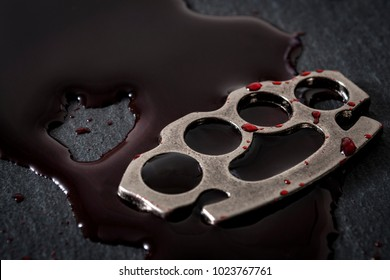 Gear and weapon used in illegal fighting, street violence and crime concept with metal knuckle sometimes called brass knuckles covered in blood with copy space